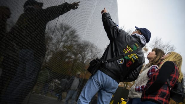 A Vietnam War veteran points to names of fallen soldiers on the wall of the Vietnam War Memorial in Washington, D.C., on November 12th, 2018.