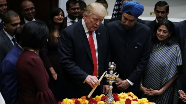 """President Donald Trump lights a """"diya,"""" or oil lamp, as Indian Ambassador to the United States Navtej Singh Sarna looks on during a Diwali ceremony in the Roosevelt Room of the White House on November 13th, 2018, in Washington, D.C. Trump was criticized online for tweets about the ceremony that mentioned Sikhs, Jains, and Buddhists but omitted Hindus, the primary celebrants of the holiday."""