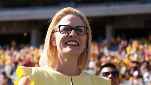 Democrat U.S. Senate candidate Kyrsten Sinema participates in the pregame coin toss before the game between the Utah Utes and the Arizona State Sun Devils at Sun Devil Stadium on November 3rd, 2018, in Tempe, Arizona.