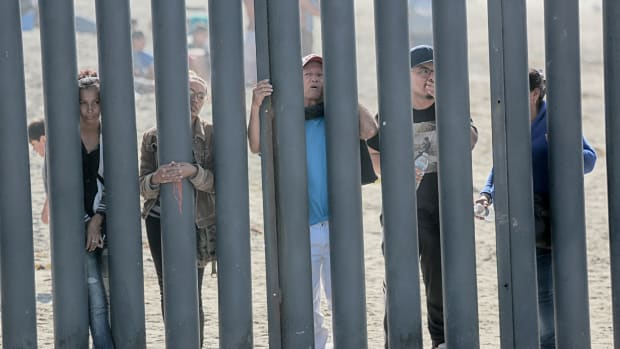 Honduran caravan members look through the fence at the United States–Mexico border wall at Friendship Park in San Ysidro, California, on November 18th, 2018.