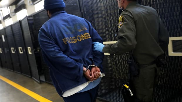 An armed California Department of Corrections and Rehabilitation officer escorts a condemned inmate at San Quentin State Prison on August 15th, 2016, in San Quentin, California.