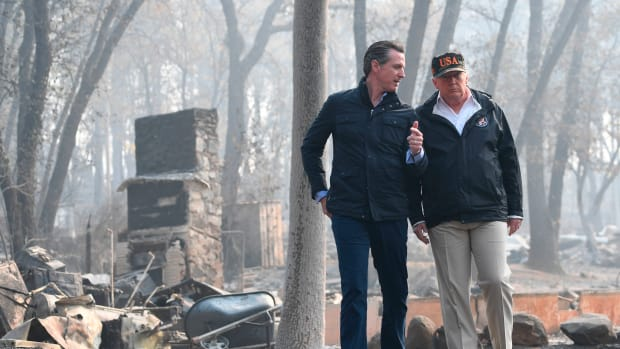 President Donald Trump speaks with Lieutenant Governor of California, Gavin Newson, as they view damage from the Camp fire in Paradise, California, on November 17th, 2018.