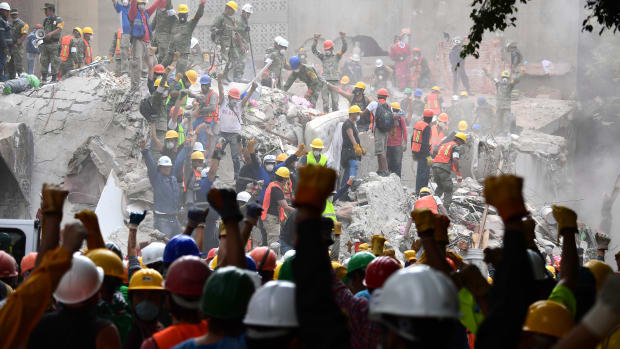 Rescuers make the signal for silence during the search for survivors in a flattened building in Mexico City on September 21st, 2017, two days after a strong quake hit central Mexico.
