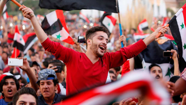 Syrians celebrate in Damascus' Umayyad Square on October 5th, 2017, after Syria's national soccer team scored in its match against Australia during the FIFA World Cup 2018 qualifier.