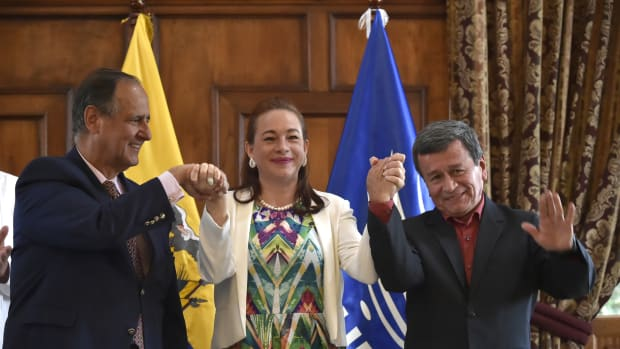 Ecuadorean Foreign Minister Maria Fernanda Espinoza raises the hands of chief negotiators Juan Camilo Restrepo and Pablo Beltran in Quito on September 4th, 2017.