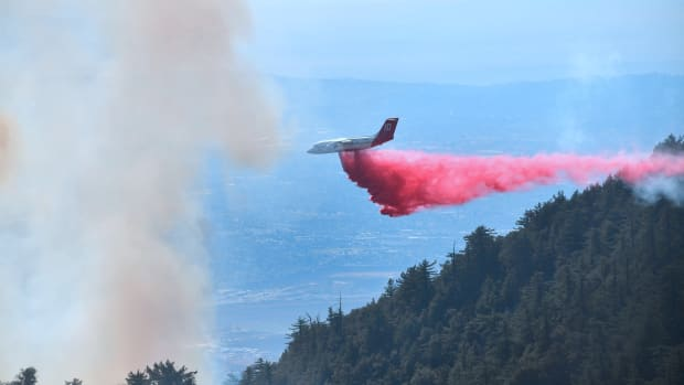 An aircraft drops fire retardant over a brush fire in the Angeles National Forest near Mt. Wilson Observatory, northeast of Los Angeles, on October 17th, 2017.