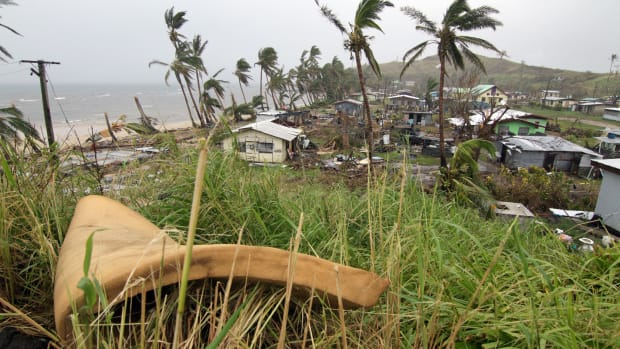 People inspect the damage from Cyclone Winston at the Namuimada settlement in Fiji on February 26th, 2016.