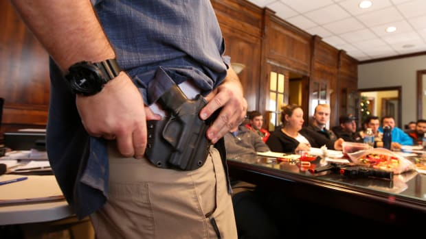 A man shows a holster at a concealed-carry permit class put on by USA Firearms Training on December 19th, 2015, in Provo, Utah.