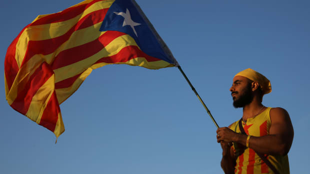 A man holds up a Catalan flag as people gather at the final pro-independence rally at Plaza Espana ahead of Sunday's referendum vote on September 29th, 2017, in Barcelona, Spain.