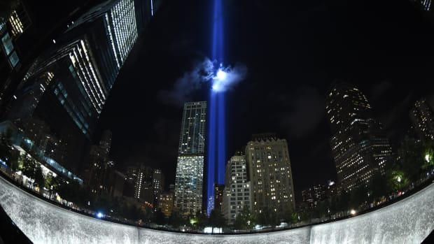 The Tribute in Light illuminates the sky behind the 9/11 Memorial waterfalls and reflecting pool in New York on September 10th, 2014.
