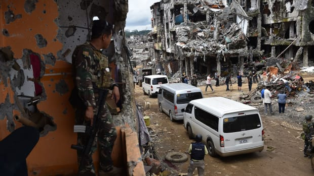 A government soldier watches as journalists tour the ruins of what was the main battle area in Marawi on the southern island of Mindanao on October 25th, 2017, days after the military declared the fighting against IS-inspired Muslim militants over.