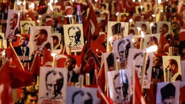 People hold torches and posters of Mustafa Kemal Ataturk, the founder of modern Turkey, during a march marking the 94th anniversary of Republic Day on October 29th, 2017, in Istanbul.