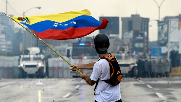 A Venezuelan opposition demonstrator waves a flag at the riot police in a clash during a protest against President Nicolas Maduro on May 8th, 2017.