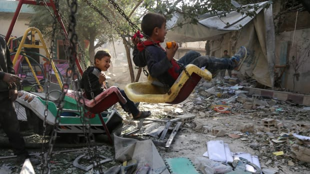 Syrian boys swing on the playground outside their damaged school on November 9th, 2017, in the besieged rebel-held Eastern Ghouta town of Hamouriyah, following air raids by government forces the previous day.