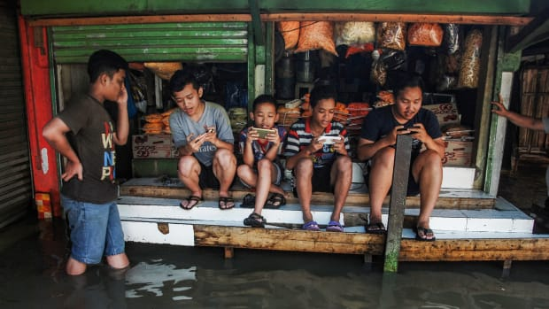 Indonesian youths play at a game center surrounded by floodwaters after seasonal rains hit Bandung on November 17th, 2017.