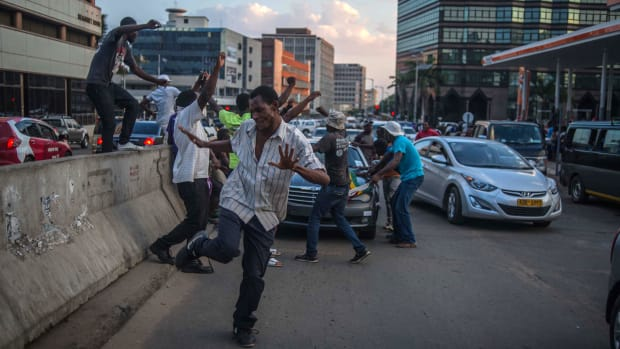 Harare residents celebrate in the streets following the resignation of Zimbabwe's president Robert Mugabe on November 21st, 2017. Mugabe, an autocrat who has ruled Zimbabwe since independence, agreed to step down a week after the military took control and moved to impeach him.