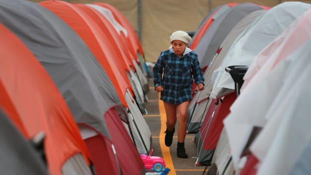 A resident of the Alpha Project campsite walks between tents.