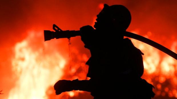 A firefighter battles a wildfire as it burns along a hillside near homes in Santa Paula, California.