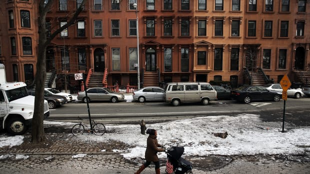 A woman and child walk down a street in the Fort Greene neighborhood where the director and artist Spike Lee once lived on February 27th, 2014, in the Brooklyn borough of New York City.