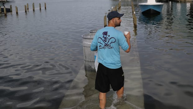 A man walks through a king tide flood in South Florida.