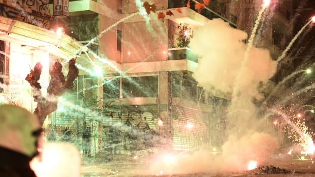 A firework explodes during clashes between protesters and police in central Athens on December 6th, 2017, at a demonstration commemorating 15-year-old Alexis Grigoropoulos, who was fatally shot by a police officer in 2008. Masked youths threw stones and vandalized property during the annual protests.