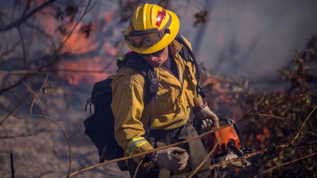 A firefighter cuts brush at the Thomas Fire on December 7th, 2017, near Fillmore, California. Strong Santa Ana winds are pushing multiple wildfires across the region, expanding across tens of thousands of acres and destroying hundreds of homes and structures.