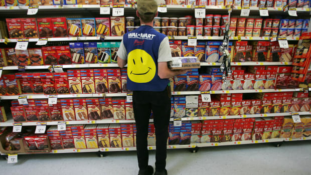 An employee restocks a shelf in the grocery section of a Walmart on May 11th, 2005, in Troy, Ohio.