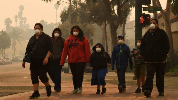 A family wears face masks as they walk through the smoke-filled streets of Ventura, California, on December 6th, 2017.