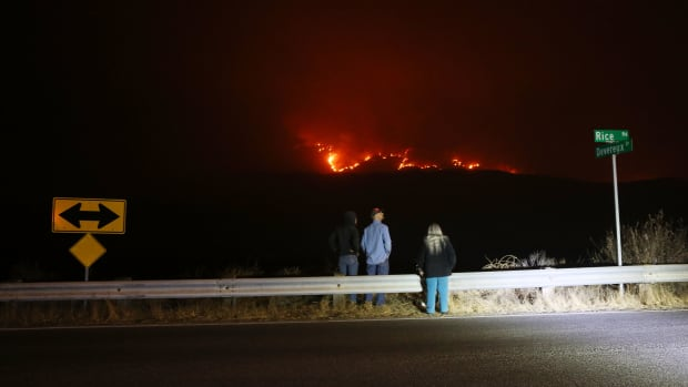 People watch from a roadside as the Thomas Fire burns in the mountains Ojai, California, on December 6th, 2017.