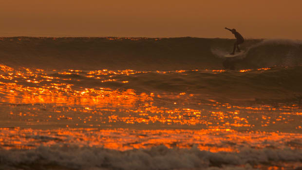 A smoke-filled sky filters orange light around a surfer as the Thomas Fire continues to grow and threaten communities from Carpinteria to Santa Barbara on December 12th, 2017, in Carpinteria, California.
