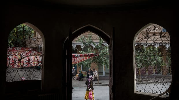 An ethnic Uyghur woman walks by a closed Islamic school on July 1st, 2017, in the old town of Kashgar, in the far western Xinjiang province, China.