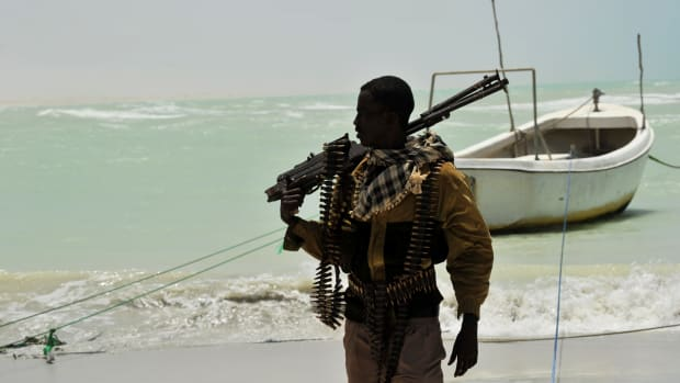 A Somali, part armed militia, part pirate, carries his high-caliber weapon on a beach in the central Somali town of Hobyo on August 20th, 2010.