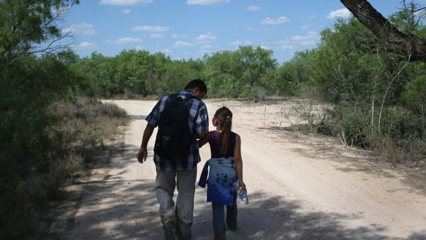 A father and his daughter walk through the South Texas countryside after crossing the Rio Grande from Mexico into the United States to seek asylum on April 14th, 2016, in Roma, Texas.