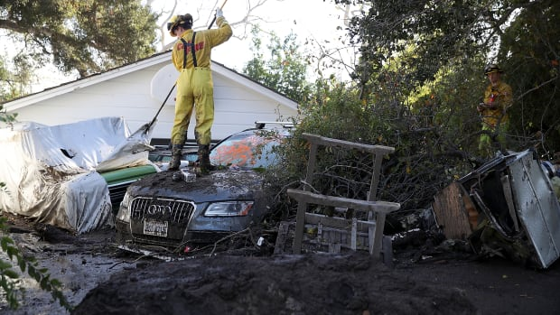 A Cal Fire firefighter looks through a car next to a home that was destroyed by a mudslide on January 12th, 2018, in Montecito, California.