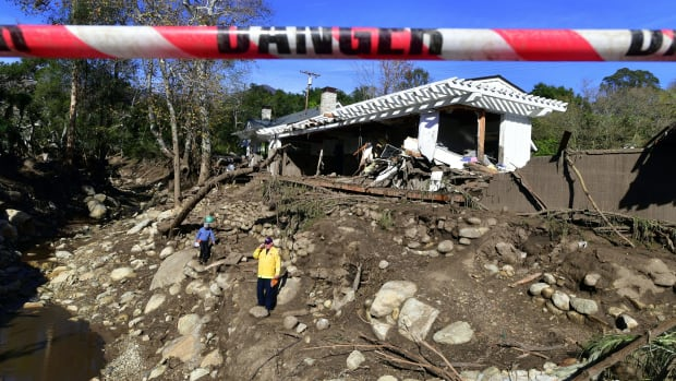 Rescue workers walk amid the debris of damaged property from mudflows carrying boulders, rocks, and uprooted trees in Montecito, California, on January 12th, 2018.