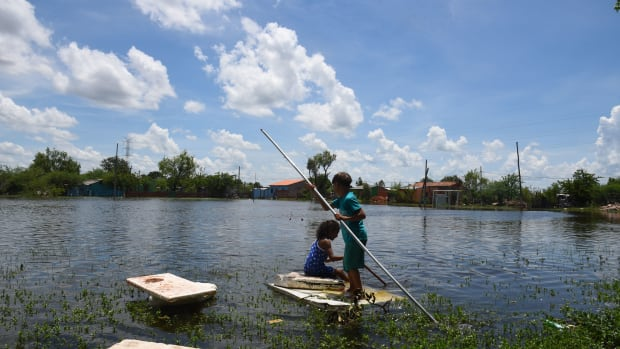 Children play in an Asunción neighborhood on January 22nd, 2018, that was flooded when the Paraguay River overflowed its banks due to heavy rains. The flooding has affected more than 18,000 people in the Paraguayan capital in the past week.
