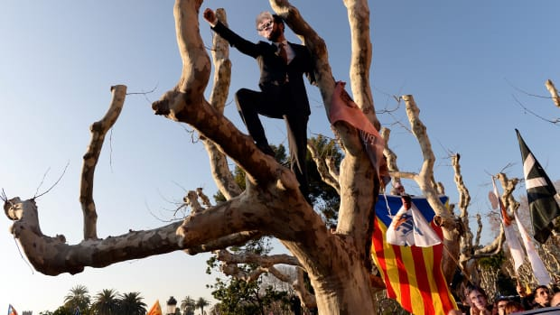 A demonstrator covers his face with a mask depicting ousted separatist leader Carles Puigdemont during a protest outside the Catalan parliament on January 30th, 2018, in Barcelona, Spain. The Parliament delayed a key debate in the regional assembly on Puigdemont's bid to form a new government, but defended his right to return to power.