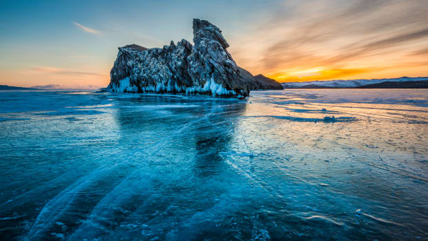 Siberia, Russia: A winter sunset near Ogoy Island on frozen Lake Baikal. With few passable roads, locals drive cars, jeeps, and even cargo lorries over the ice to shorten their journeys.