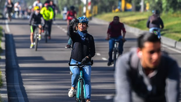 A woman takes a picture while riding her bike during a car-free day in Bogotá, Colombia, on February 1st, 2018. Residents of Bogotá were encouraged to use alternative means of transportation during a car-free day in an attempt to reduce environmental pollution.