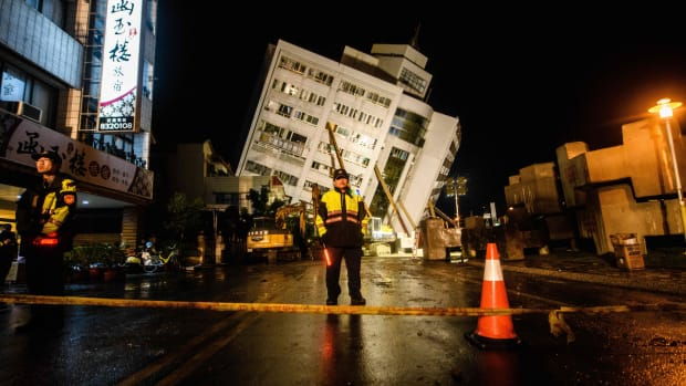 Rescue workers stand guard in front of a cordon as the Yun Tsui apartment building leans to one side after an overnight earthquake in Hualien, Taiwan, on February 7th, 2018.