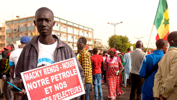 A man carries a placard demanding election rights during a demonstration by opposition parties for free and transparent elections on February 9th, 2018, in Dakar, Senegal. Senegal's presidential elections will be held in 2019.