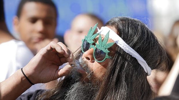 Fast Eddy Aki'a of Hawaii smokes a joint as thousands gathered to celebrate Colorado's medicinal marijuana laws on April 20th, 2012, in Denver, Colorado.