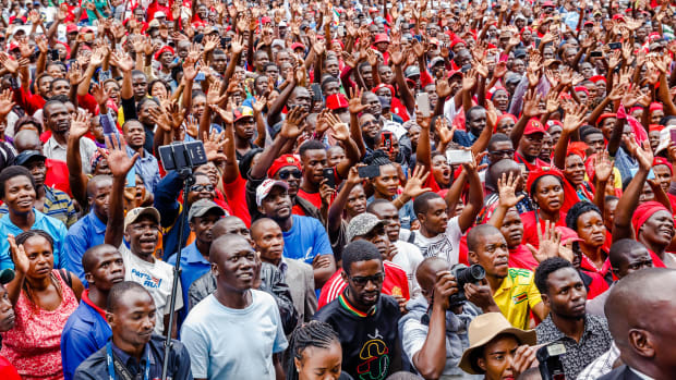 Supporters of the Zimbabwe opposition party, the Movement for Democratic Change, listen and cheer as the party's acting president addresses the crowd gathered outside the party headquarters in Harare, Zimbabwe, on February 15th, 2018, following the death of the former opposition leader, Morgan Tsvangirai.
