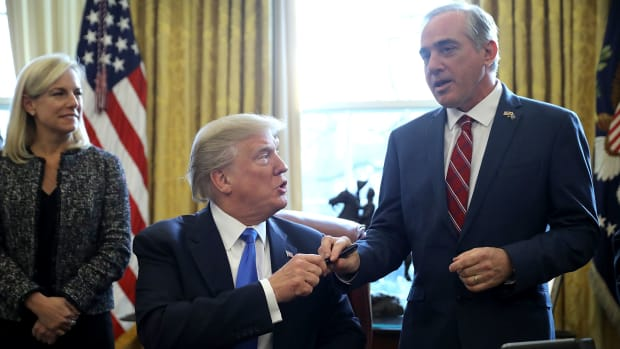 U.S. President Donald Trump gives the pen he used to sign an executive order supporting veterans as they transition from military to civilian life to Veterans Affairs Secretary David Shulkin.