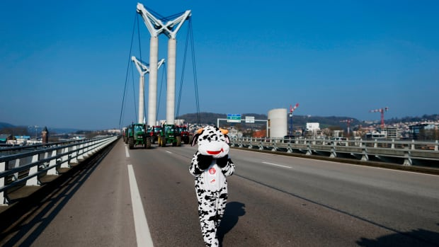 A person in a cow costume walks near farmers in their tractors, which block Gustave-Flaubert Bridge in Rouen, France, during a demonstration on February 21st, 2018, to protest against the trade deal negotiations in Brussels between Mercosur and the European Union. The negotiations include a revision of the map of disadvantaged areas through which certain communes receive aid.
