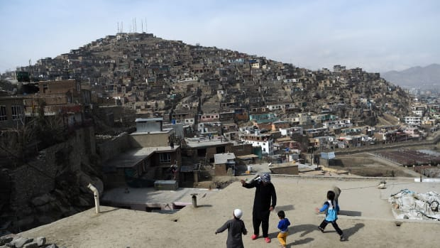 An Afghan man and children play with a kite on a rooftop overlooking Kabul, the capital city of Afghanistan, on February 23rd, 2018.