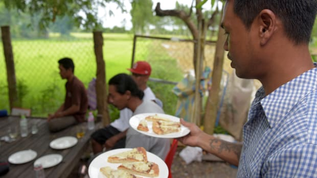 Nheb Thai, a Cambodian refugee who was deported from the U.S., carries plates with pizza as he serves a meal to a group of other deportees in Cambodia.