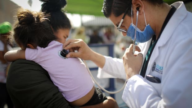 A Honduran mother holds her daughter, who fell ill, while being examined by a doctor outside a shelter for migrants on November 21st, 2018, in Mexicali, Mexico.