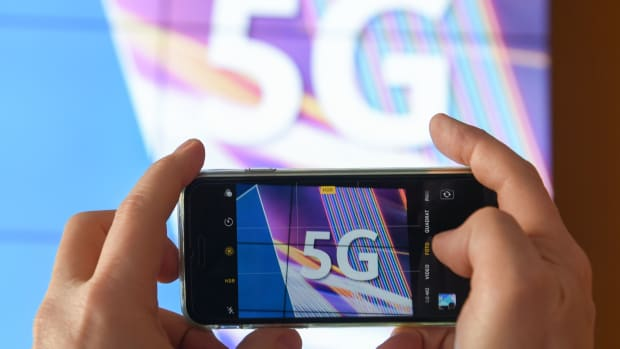 A journalist takes pictures of a projection screen prior to the start of Germany's auction for the construction of an ultra-fast 5G mobile network.