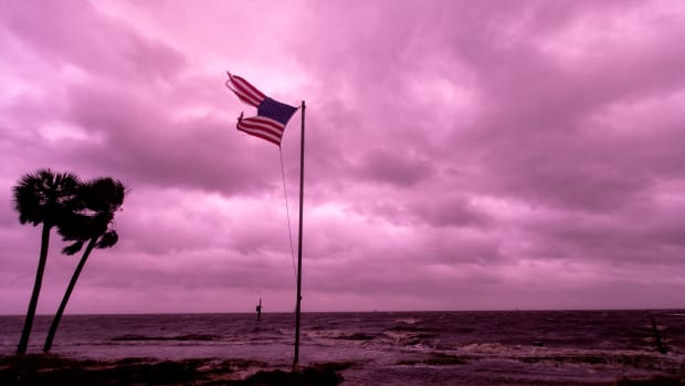 An American flag battered by Hurricane Michael waves against a rose-colored light of sunset at Shell Point Beach on October 10th, 2018, in Crawfordville, Florida.